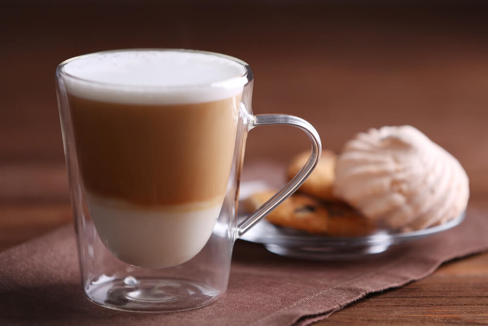 A Mocha Latte with a plate of biscuit seen in the background.