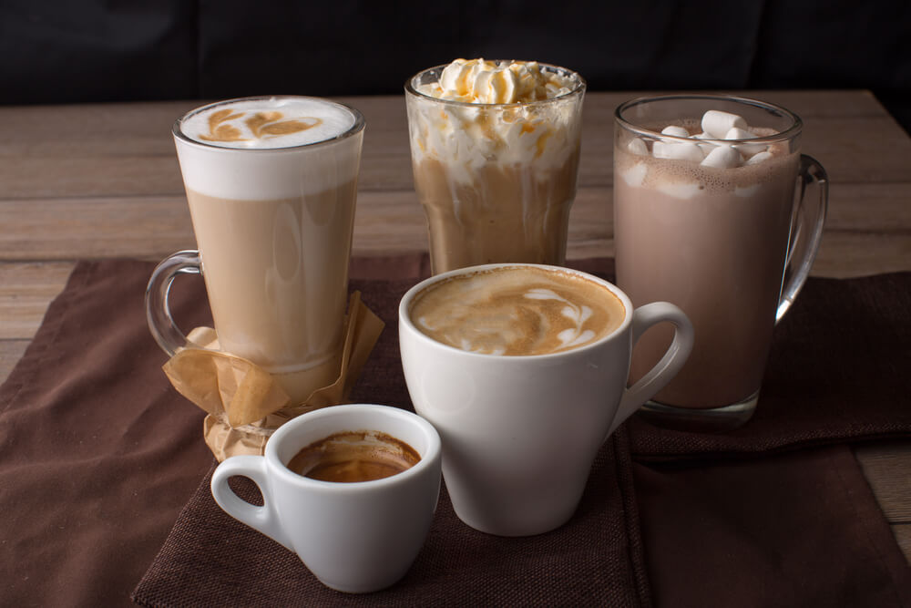 different mocha drinks laid on top of a brown table napkin