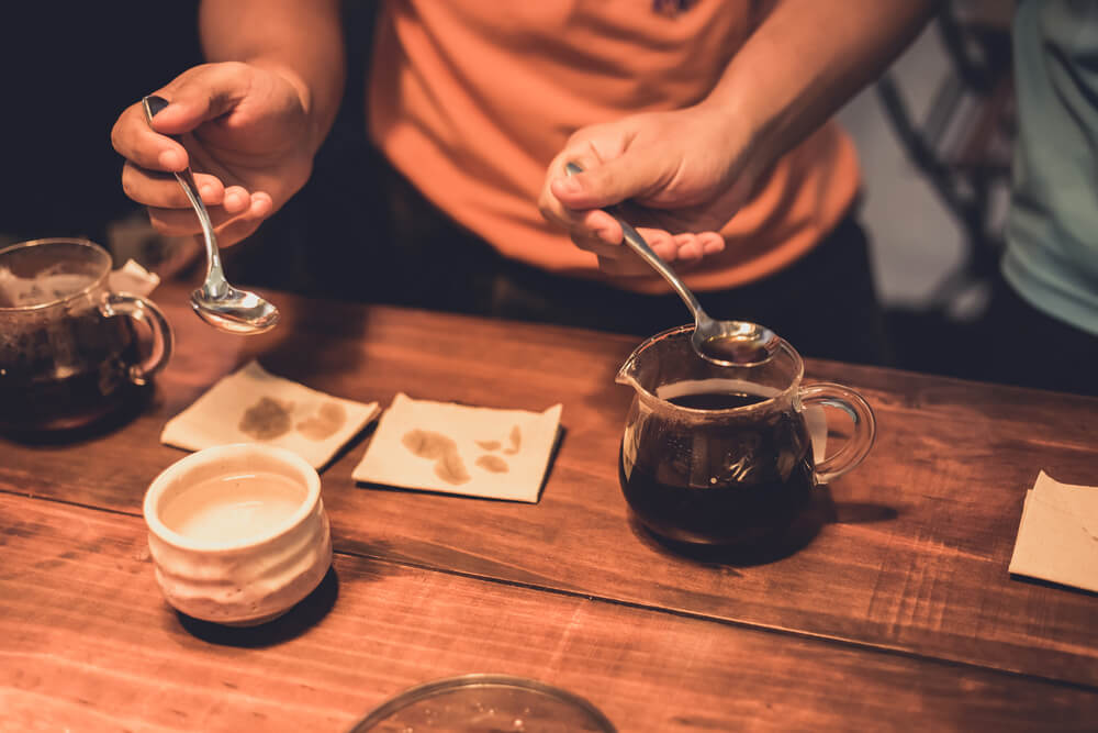 Barista using two spoon during coffee cupping