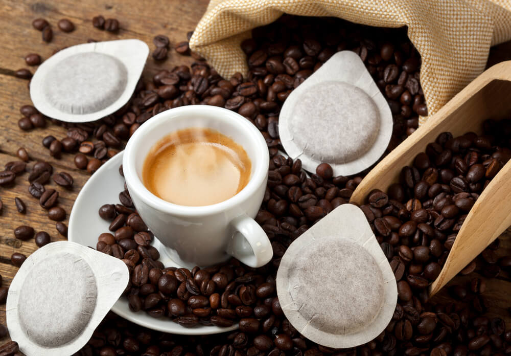 A coffee cup surrounded with coffee beans and coffee pods