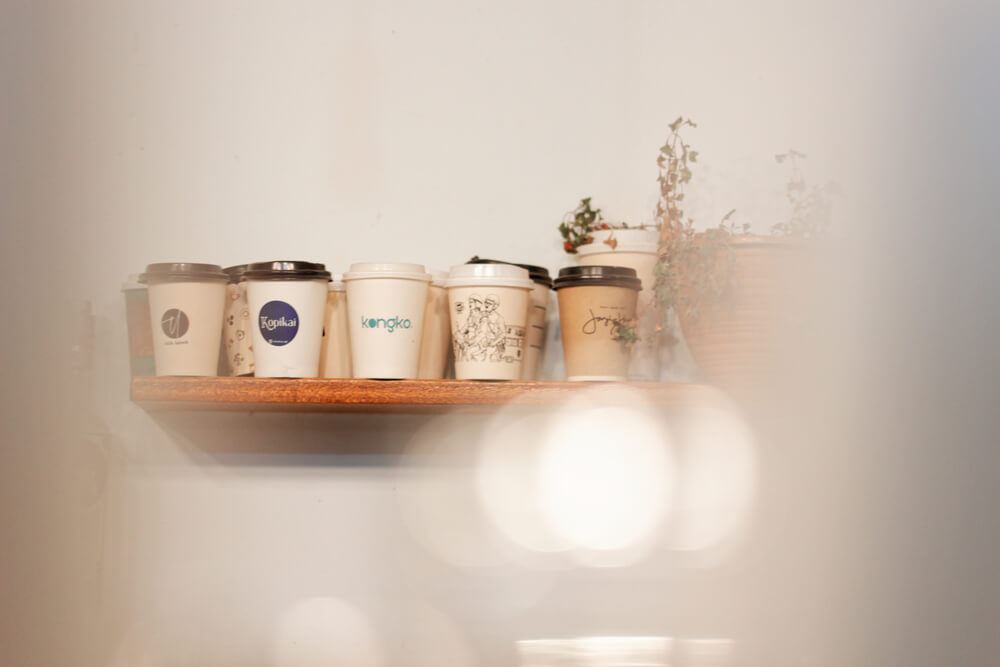 A collection of eco-friendly coffee cups from various local brands displayed on wall shelves
