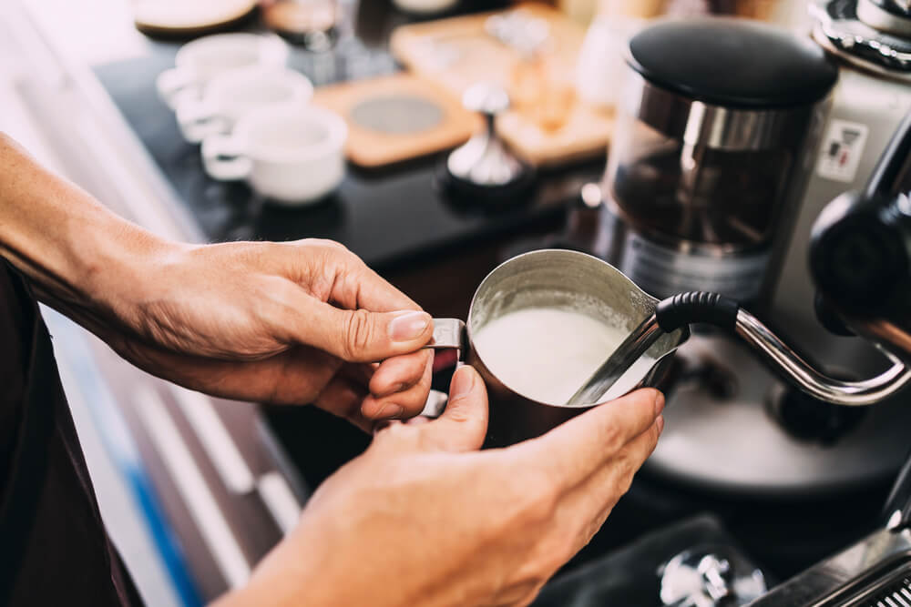 Close-up barista hands frothing warm milk on a coffee machine