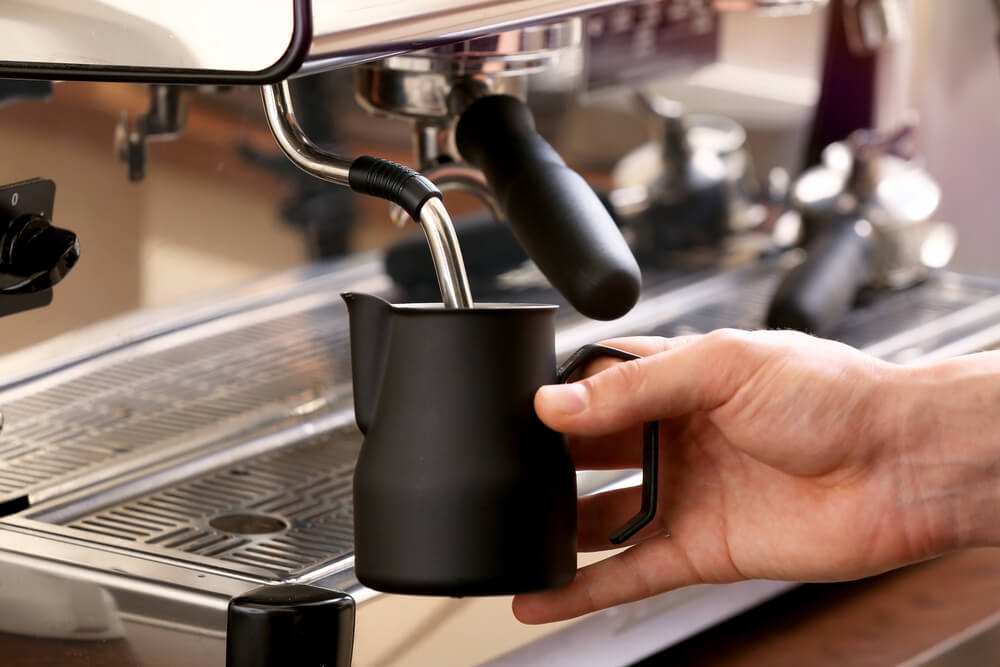 Barista whipping milk using the best milk frothing pitcher that is color black.
