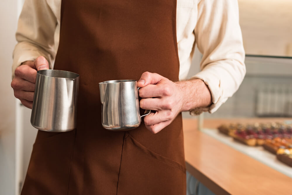 barista in brown apron holding steel milk jugs