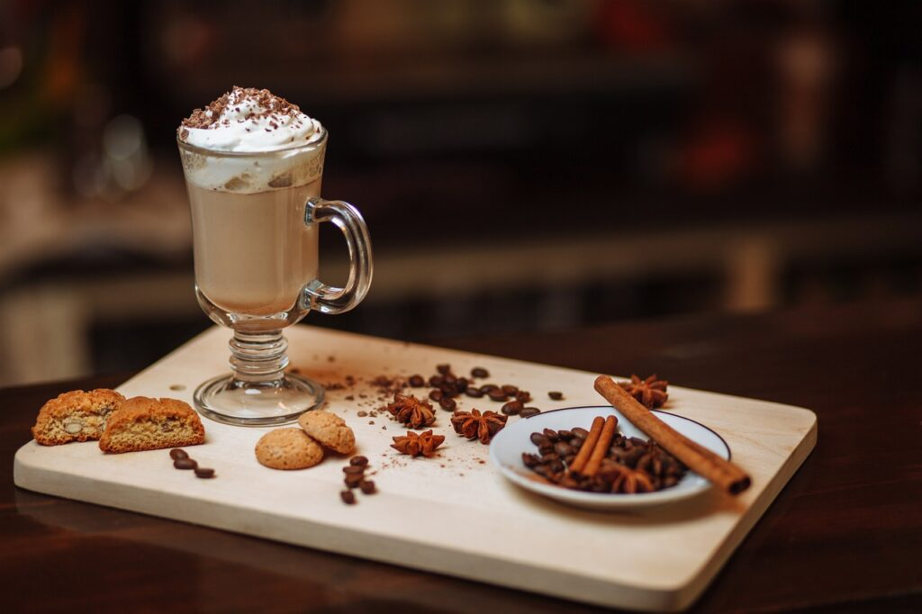 mocha cofee drink with cinnamon, star anise, coffee beans, and cookies in a wooden board