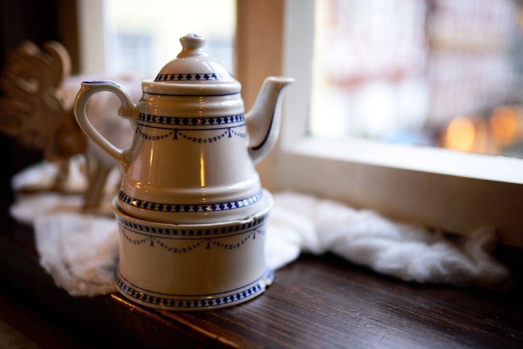 a ceramic coffee pot near a window
