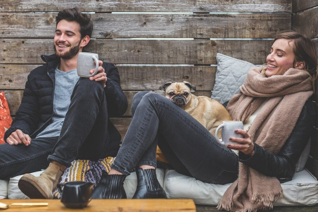 man and woman drinking coffee in a cabin together with a dog