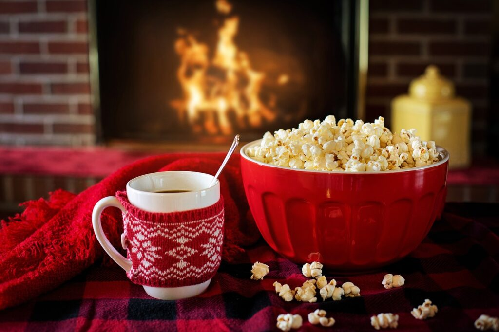 a white coffee mug with wrap with tea cozy beside a bowl of popcorn
