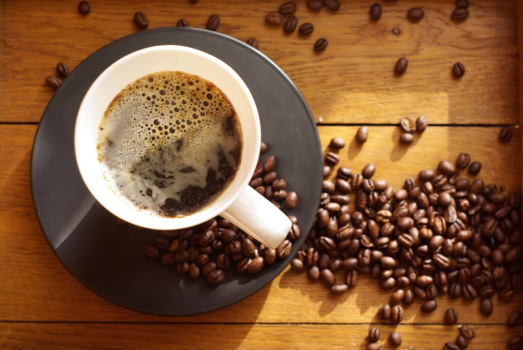Best coffee for black coffee. A top view of a cup of coffee in a saucer with coffee beans on the table.