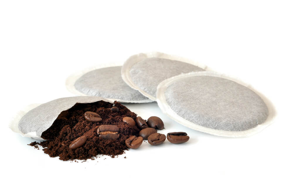 Four white coffee pods with the contents of one pod exposed.