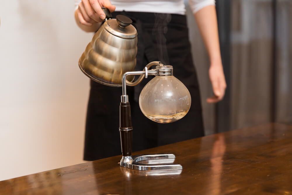 a man pouring coffee using siphon coffee maker
