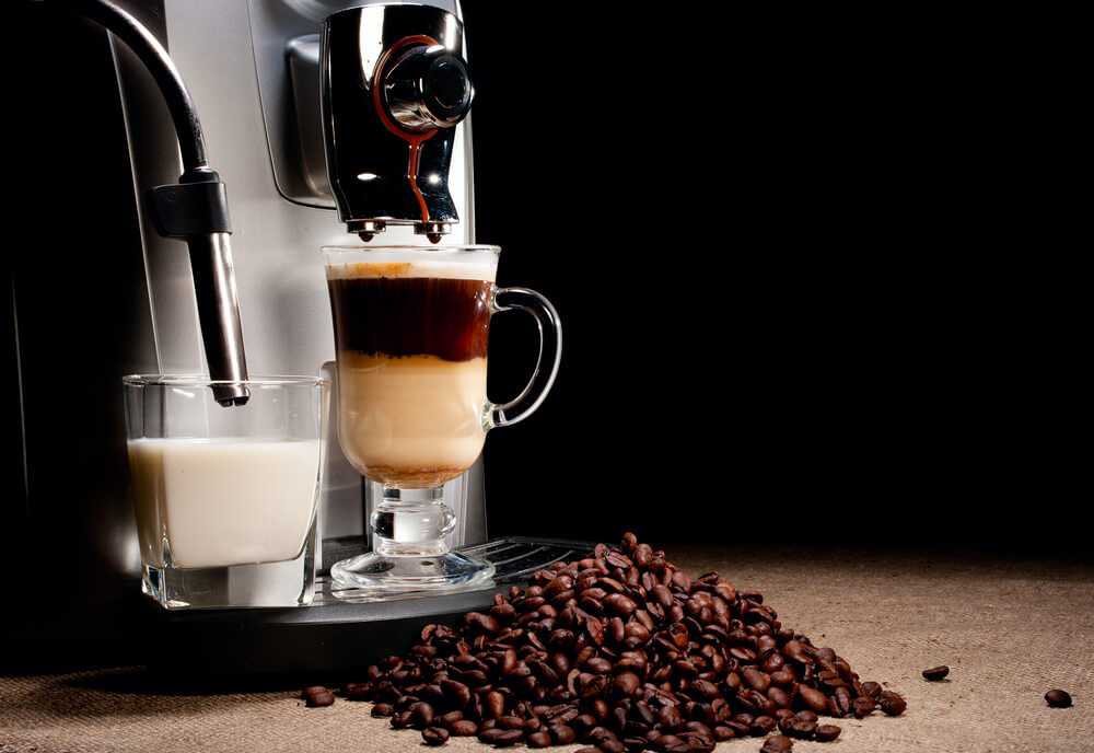 auto-drip coffee maker with cup of coffee and coffee beans