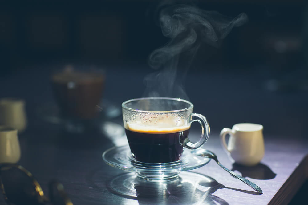 cup of hot brew coffee with a spoon on a table