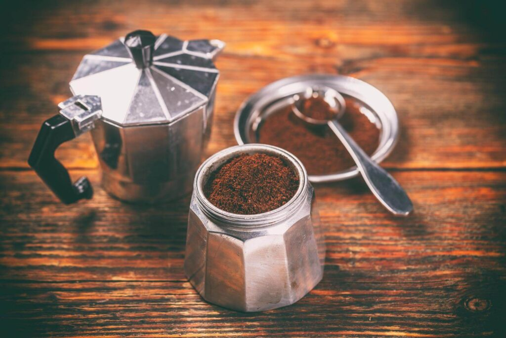 Moka pot and ground coffee with a scoop