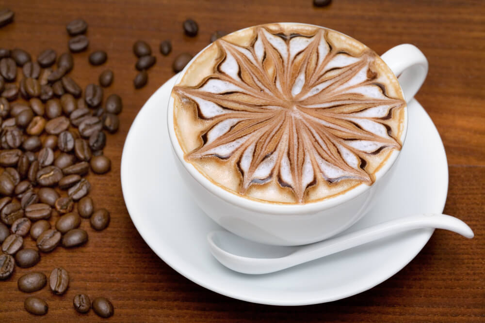 How do you keep frothed milk frothed. Top view of a cup of frothed milk with flower art.