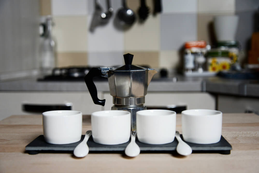 Moka pot and three coffee cups