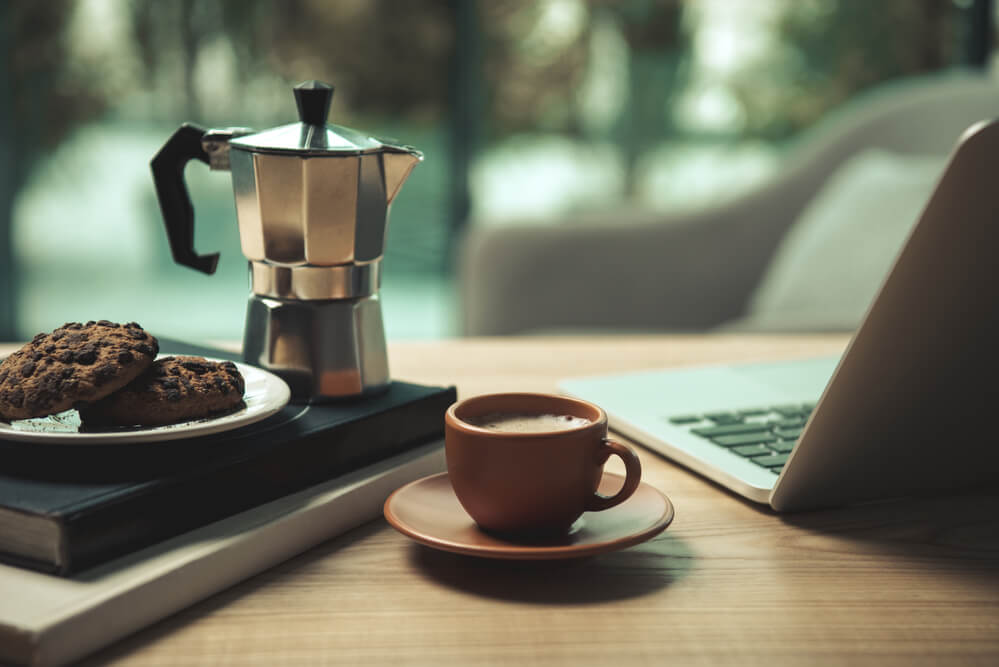 moka pot and a cup of coffee with laptop and cookies